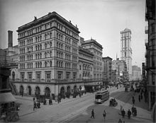 A tall, imposing stone building in an almost empty city street with tramcar passing. A tower in the background is the only other highrise building.