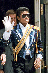 A man wearing dark sunglasses and a jacket covered in blue and yellow rhinestones, holding up his right hand which is covered in a white glove. Behind him stands a man in a black suit.