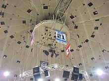Photo de la bannière dédiée à Michel Briere au milieu de câbles tombant du plafond de la Mellon Arena; on distingue également les drapeaux américains, canadiens et la bannière dédiée à Mario Lemieux.