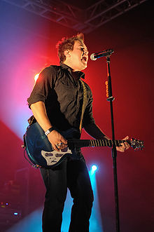 A twenty-something male sings into a standing microphone at a concert venue while playing his electric guitar. Red background lights shine on him.