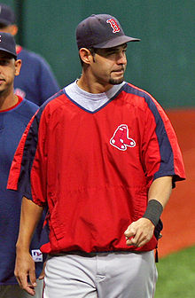 "A white male baseball player with facial hair, wearing a blue cap with a red ""B"" on it, a red polyester shirt, and white pants, looks to his left."