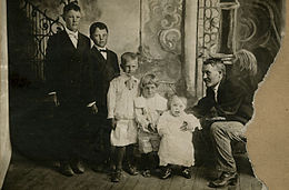 Five children standing in descending order of age and height, adult male sitting next to the youngest one