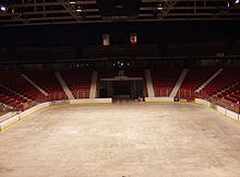 An empty arena with the sheet of ice and the score board