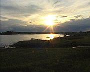 The sun low over the horizon over a body of water surrounded by dark vegetation