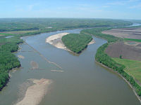 Aerial view of a brownish river winding through an agricultural valley