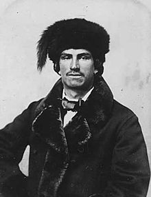 Black and white photograph of a man with a short moustache and earings, wearing a fur lined dress jacket, bow tie and fur hat