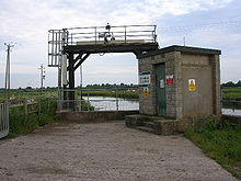A metal gantry between the road in the foreground and a river. To the right is a breeze block building with warning signs on it.