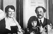 family group of young brunette mother, daughter of about six years old, and father with mid-length dark hair and walrus moustache