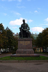 A statue of a tall man with a long beard and glasses, seated, a large musical score open in his lap