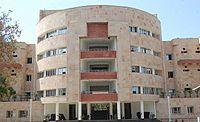 Four-story, round, light-coloured building