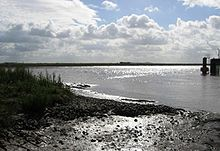 Muddy bank in the foreground before an expanse of water, with a concrete wall just visible on the right hand side of the water. In the distance is a line of low hills.
