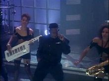 An African American man. He is surrounded by two women playing instruments. He is wearing a black suit and a headset, while performing on a stage with the women. The women are wearing black lace outfits.