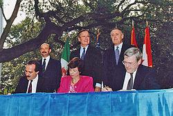 Photographie des premiers ministres du Canada, des États-Unis et du Mexique debout derrière les trois ministres du Commerce international de ces pays, signant l'Accord de libre-échange nord-américain.