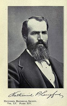 A middle-aged man in formal attire with a beard