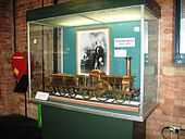 A glass display case containing a large brass model of a steam locomotive. At the back of the case is a black and white photograph of a man.
