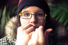 A young woman bites her fingernails.