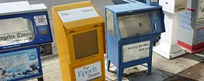 Empty newspaper vending boxes on the street, left to right, the Los Angeles Times (cut off), Epoch Times, a San Diego paper (Gone to the Web, sddt.com), a white unnamed box, and the San Diego Business Journal (cut off)