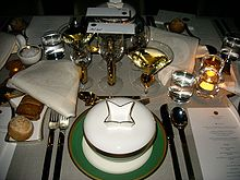 A set table with a white table cloth. There are many plates and glasses plus a menu visible on the table.