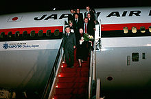 Japan Prime Minister Noboru Takeshita and eleven others deplanes on steps in red colour, from a Japan Air Lines DC-10 marked with an Official Airline for Expo '90 Osaka, Japan logo and text