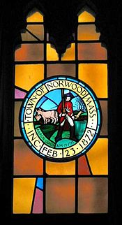 Stained-glass window in Norwood town hall depicting town seal. It was suggested in 2006 that Guild's red coat must surely be historically inaccurate.[10]