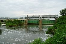 Metal gates surmounted by a gantry across the river. To the left is a weir.