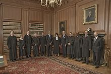 Nine judges in black robes pose for a photograph with three other men in suits.