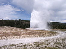 High geyser of water erupts out of the sparsely vegetated earth.