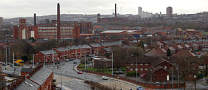 A view of a busy townscape, in which the land is urban and the scene is banal. The weather is overcast and the cloudy sky appears light-grey. In the foreground is a dark-grey tarmac dual-carriageway road, which sweeps up the middle of the photograph to its centrepoint. All around the road are two-storey red-brick houses. On the left-side of the midground are three large red-brick factories of around five-storeys high. On the horizon is a towerblock.