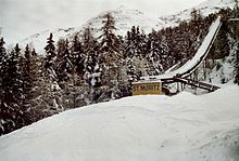 """A snow-covered ski jump with the words, """"St. Moritz"""" at the base"""