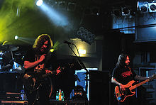 Two men with long hair are on a stage. One plays a shiny guitar and the other plays a bass guitar with a wood finish