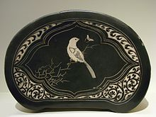An oval shaped pillow with flat sides. It is made of black cloth with an image of a white bird sitting on a branch stitched into it.