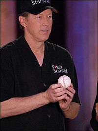 A tanned male baseball player in his fifties wearing a black cap and shirt, holding a baseball.