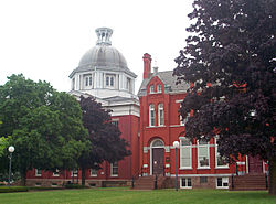 Two red buildings, both slightly obscured by trees in front of them. The one on the left has a metallic dome, the one on the right has a pointed roof with chimney