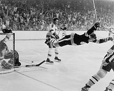 Group of hockey players. A hockey player in black is raised a few feet off the ice with his hands raised in excitement.
