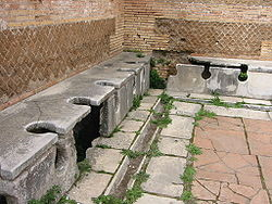 Photographie de toilettes publiques romaines (latrines), dans le port antique d'Ostie.
