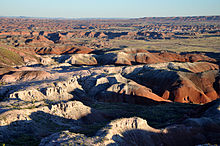 An eroded multi-colored landscape of rounded buttes and small arroyos stretches into the distance under a blank sky.