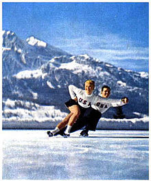A man and woman in figure skating attire skating on ice.