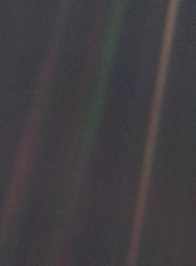 Dark grey and black static with coloured vertical rainbow beams over part of the image. A small pale blue point of light is barely visible.