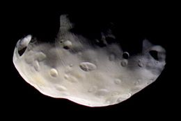An irregularly shaped body is half illuminated from the bottom. The terminator runs from the left to right. The surface is covered by numerous craters.
