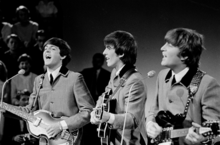 A black-and-white image of Paul McCartney, George Harrison, and John Lennon playing guitars and wearing matching grey buttoned-up suit jackets with ties underneath. An audience is visible behind them on the left.