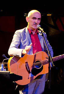 56-year-old Kelly is standing at a microphone with his guitar slung over his shoulders. His right arm is bent at the elbow towards the viewer, while his left is at his hip. He wears a gray suit with an orange shirt.