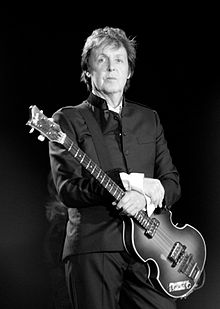 Black and white photgraph of McCartney standing onstage holding a bass guitar. He is wearing a dark suit.