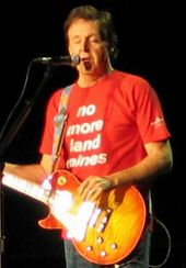 """McCartney, in his late sixties, playing an orange electric guitar and wearing a red shirt that bears, in white writing, the words """"no more land mines."""" His eyes are closed."""