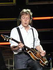 Colour photograph of McCartney, in his sixties, playing a Höfner 500/1 electric bass. He wears a black buttoned-up suit jacket with black pants.