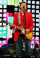 A colour photograph of McCartney, wearing a red coat and blue jeans playing an electric guitar and singing while performing live on a stage.