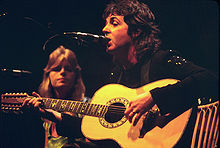 McCartney, seated, playing a twelve-string acoustic guitar, Linda McCartney can be seen seated to his right.