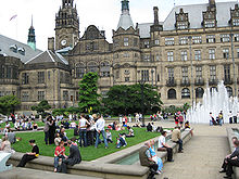 View across a garden containing people enjoying a sunny day towards a large Victorian building with a clock tower