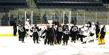 Photo de joueurs entourant un entraîneur qui leur parle.