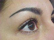 Œil et sourcil de femme, avec tatouage figurant un maquillage permanent sur le sourcil
