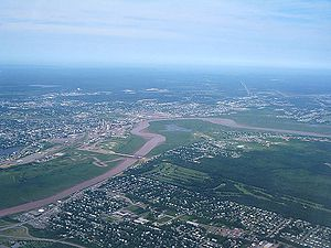 An overhead view shows a river winding through the city of Moncton. There is parkland and a golf course near the water, and city streets further out.